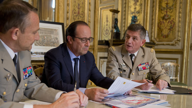 French president Francois Hollande (C) attends a meeting focused on the Iraqi conflict with French Army Chief of Staff General Pierre de Villiers and French President's chief of staff general Benoit Puga at the Elysee palace in Paris on Oct. 1, 2014. (Alain Jocard/AFP/Getty Images)