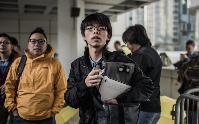 Hong Kong student activist Joshua Wong (C) is pictured outside the High Court in Hong Kong on Jan. 8, 2015. (Philippe Lopez/AFP/Getty Images)