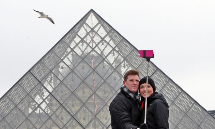 Chris Baker and Jennifer Hinson from Nashville, Tennessee, use a selfie stick in front of the Louvre Pyramide in Paris, Tuesday, Jan. 6, 2015. (AP Photo/Remy de la Mauviniere)