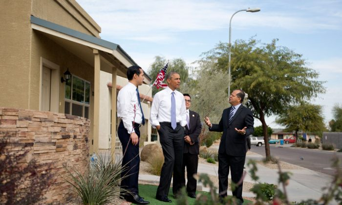 President Barack Obama, joined by Housing and Urban Development Secretary Julian Castro (L), and Chicanos Por La Causa's Edmundo Hidalgo (R), and David Adame, looks out over a housing development in Phoenix, Thursday, Jan. 8, 2015. (AP Photo/Carolyn Kaster)