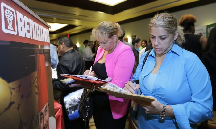 Job seekers Madelin Garcia (R) and Noharis Nunez fill out a job applications near a Benihana booth at a job fair in Miami Lakes, Fla., on Oct. 22, 2014. With the price of oil below $50 a barrel, consumers will have steadily more money to spend, potentially creating job openings at retailers, auto dealers, shipping firms, restaurants and hotels. (AP Photo/Alan Diaz)