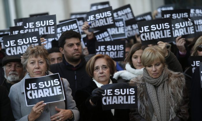 "People holding paper with a slogan that reads in French: ""I am Charlie"" observe a minute of silence outside the Lisbon's City Hall, in honor of the people killed during the attack by gunmen at the French newspaper Charlie Hebdo's offices in Paris, in Lisbon, Thursday, Jan. 8, 2015. From Berlin to Bangkok, tens of thousands took a stand Thursday against living in fear, as rallies defended the freedom of expression and honored the victims of a Paris newspaper attack. (AP Photo/Francisco Seco)"