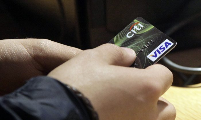 A Visa credit card is tendered at opening of the Superdry store in New York's Times Square on May 9, 2012. The Federal Reserve releases its November report on consumer borrowing on Thursday, Jan. 8, 2015. (AP Photo/Richard Drew)