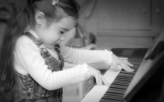A stock photo of a child playing the piano (Shutterstock*; edited by Epoch Times)