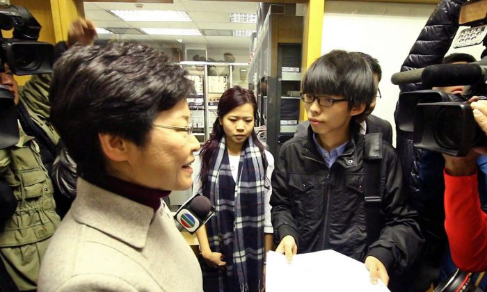 Scholarism leader Joshua Wong hands Chief Secretary Carrie Lam a junior high grading guide at the Commercial Radio office on Thurs., Jan. 8, 2015. (Choi Man Man/Epoch Times)