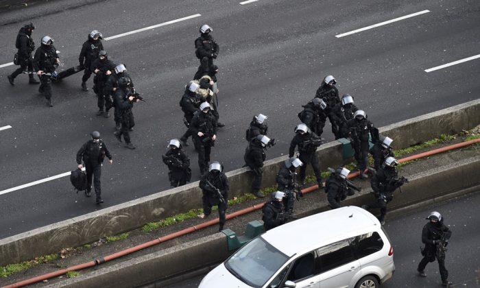 Members of the French police special force RAID walk on the 'peripherique' (circular road) in Porte de Vincennes, eastern Paris, on Jan. 9, 2015, before taking their positions after at least one person was injured when a gunman opened fire at a kosher grocery store on Jan. 9 and took at least five people hostage, sources told AFP. The attacker was suspected of being the same gunman who killed a policewoman in a shooting in Montrouge in southern Paris on Jan. 8. (Eric Feferberg/AFP/Getty Images)