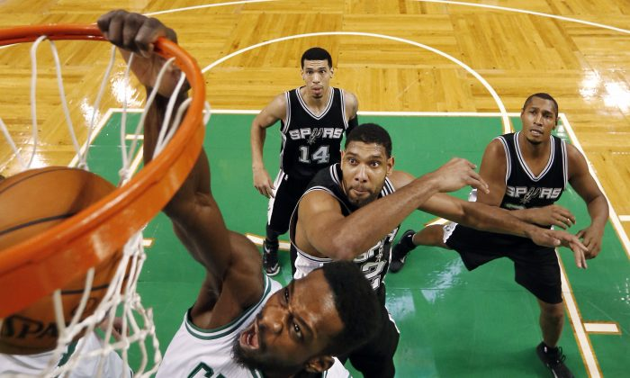Boston Celtics' Jeff Green dunks on San Antonio Spurs' Tim Duncan during the first half of an NBA basketball game in Boston, Sunday, Nov. 30, 2014. San Antonio won 111-89. (AP Photo/Winslow Townson)