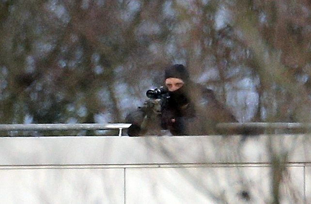 A hooded police officer aim from a rooftop in Dammartin-en-Goele, northeast of Paris, where the two brothers suspected in a deadly terror attack were cornered, Friday, Jan. 9, 2015. Two sets of attackers seized hostages and locked down hundreds of French security forces around the capital on Friday, sending the city into fear and turmoil for a third day in a series of linked attacks that began with the deadly newspaper terror attack that left 12 people dead. (AP Photo/Christophe Ena)