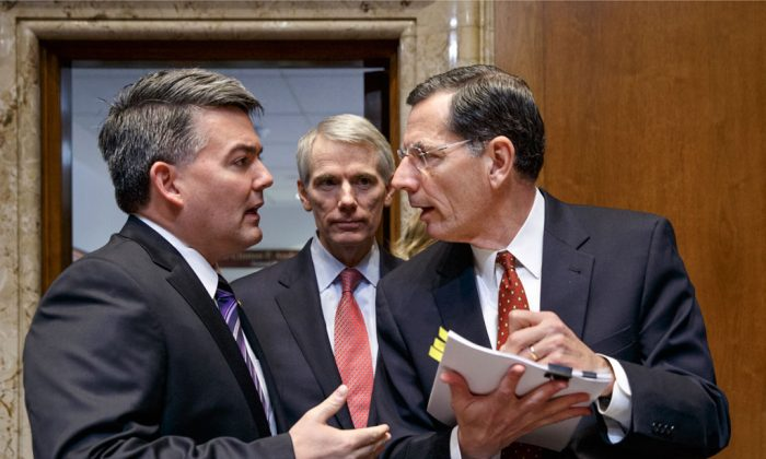 Senate Energy and Natural Resources Committee members, (L-R) Sen. Cory Gardner (R-Colo.), Sen. Rob Portman (R-Ohio), and Sen. John Barrasso (R-Wyo.) confer on Capitol Hill in Washington, Thursday, Jan. 8, 2015, as the committee crafts a markup of the long-stalled Keystone XL pipeline bill. The bill, at the top of the GOP agenda, was passed out of the committee and will go to the Senate floor for debate. (AP Photo/J. Scott Applewhite)