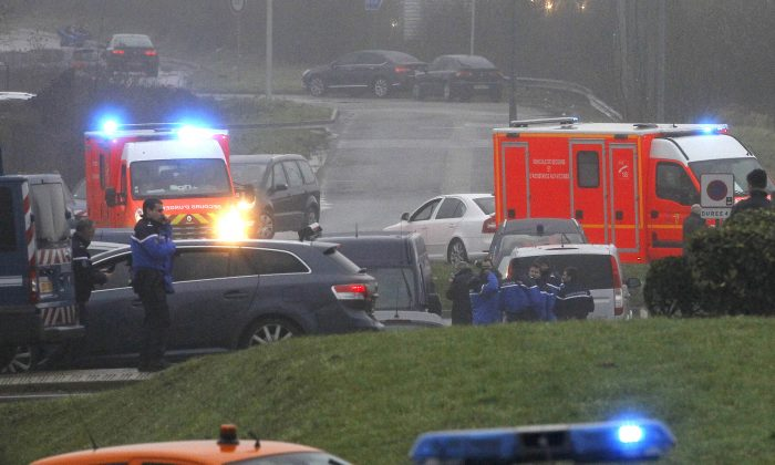 Ambulances arrive in Dammartin-en-Goele, northeast Paris, as part of an operation to seize two heavily armed suspects, Friday, Jan. 9, 2015. French security forces swarmed a small industrial town northeast of Paris Friday in an operation to capture a pair of heavily armed suspects in the deadly storming of a satirical newspaper. Shots were fired as the brothers stole a car in the early morning hours, said a French security official, who could not immediately confirm reports of hostages taken or deaths later in the day in the town of Dammartin-en-Goele, about 40 kilometers (25 miles) northeast of Paris. (AP Photo/Michel Spingler)