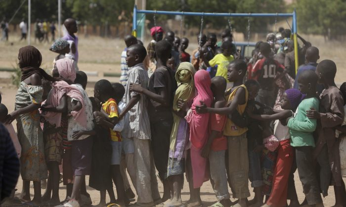 Children displaced after attacks by Boko Haram, line up in the camp of internal displace people, in Yola, Nigeria, on Nov. 27, 2014. (AP Photo/Sunday Alamba)