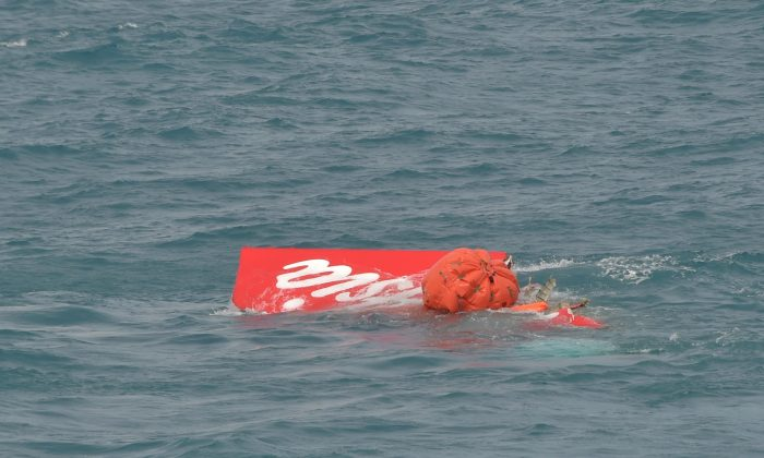 Portion of the tail of AirAsia Flight 8501 floats on the water as Indonesian navy divers conduct search operations for the black boxes of the crashed plane in the Java Sea, Indonesia, Saturday, Jan. 10, 2015. Investigators searching for black boxes in the crashed AirAsia plane lifted the tail portion out of the Java Sea on Saturday, two weeks ago after it went down, killing all 162 people on board. (AP Photo/Adek Berry, Pool)