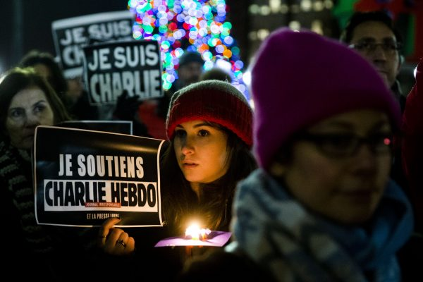 People gather to pay to pay tribute to victims of the terrorist attack against the French satirical weekly Charlie Hebdo, Friday, Jan. 9, 2015, at JFK Plaza, commonly known as Love Park, in Philadelphia. (AP Photo/Matt Rourke)