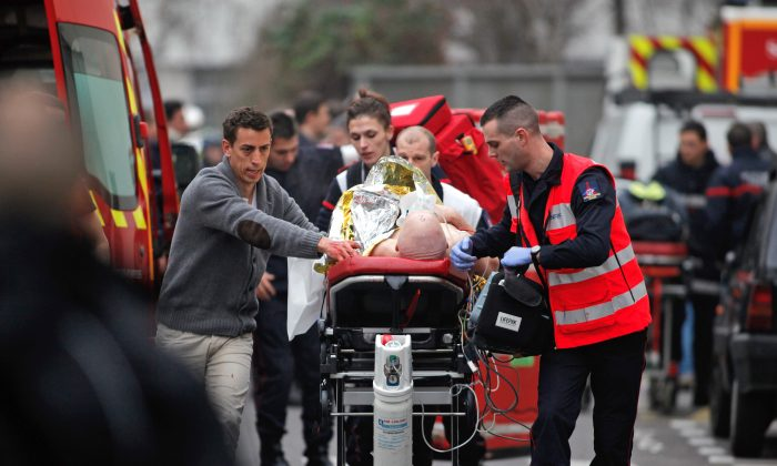 An injured person is transported to an ambulance after a shooting at the French satirical newspaper Charlie Hebdo's office in Paris, France, Jan. 7, 2015. (AP Photo/Thibault Camus)