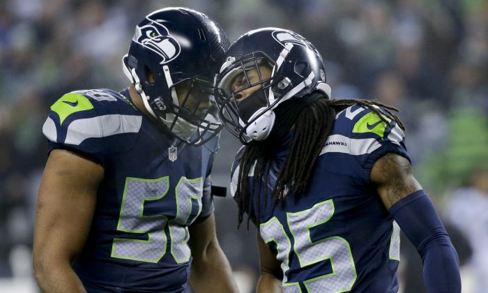 Seattle Seahawks cornerback Richard Sherman, right, celebrates after intercepting a pass by Carolina Panthers quarterback Cam Newton with outside linebacker K.J. Wright (50) during the first half of an NFL divisional playoff football game in Seattle, Saturday, Jan. 10, 2015. (AP Photo/Elaine Thompson)