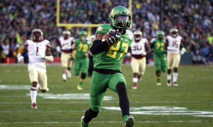 In this Jan. 1, 2015, file photo, Oregon wide receiver Darren Carrington scores against Florida State during the second half of the Rose Bowl NCAA college football playoff semifinal in Pasadena, Calif. (AP Photo/Lenny Ignelzi, File)