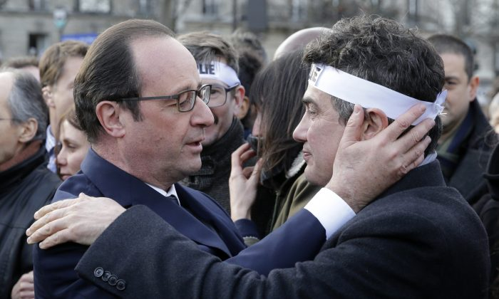 French President Francois Hollande, left, comforts French columnist for Charlie Hebdo Patrick Pelloux as they take part with family members and relatives in a solidarity march in the streets of Paris, France, Sunday, Jan. 11, 2015. A rally of defiance and sorrow, protected by an unparalleled level of security, on Sunday will honor the 17 victims of three days of bloodshed in Paris that left France on alert for more violence. (AP Photo/Philippe Wojazer, Pool)