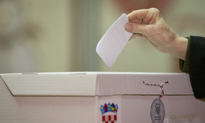 A voter casts his ballot at a polling station in Zagreb, Croatia, Sunday, Jan. 11, 2015. A liberal incumbent and a conservative rival are heading into a surprisingly close showdown in Croatia's presidential runoff held amid deep discontent over economic woes in the European Union's newest member. (AP Photo/Darko Bandic)