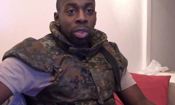 """This image mahostage-taker Amedy Coulibaly, who shot a policewoman and four hostages at a kosher grocery in Paris, speaking in broken Arabic that he seems to be reading from a paper, in front of an Islamic State emblem, as he defends the attacks carried out on the satirical newspaper Charlie Hebdo, police and the Jewish store. At one point, Coulibaly says Charlie Hebdo will be attacked """"tomorrow"""" and that he and the (Said and Cherif Kouachi) brothers were coordinating. (AP Photo/Militant Video)"""