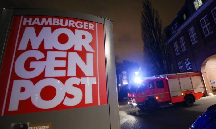 A firef truck sits outside the building of the 'Hamburger Morgenpost' in Hamburg, northern Germany, Sunday morning, Jan. 11, 2015. According to police fire broke out in an archive room of the paper after an arson attack. The newspaper ran caricatures of the Charlie Hebdo newspaper after the attack on Wednesday. (AP Photo/dpa, Bodo Marks)