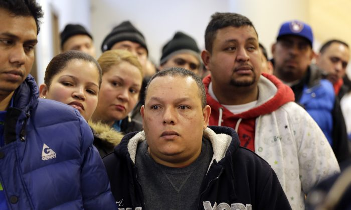 People wait in line to apply for municipal identification cards on the first day they are available at the Bronx Library Center in New York on Monday, Jan. 12, 2015. The card is aimed at those who don't currently have an ID. That includes an estimated 500,000 immigrants in the city without legal documentation. (AP Photo/Mark Lennihan)