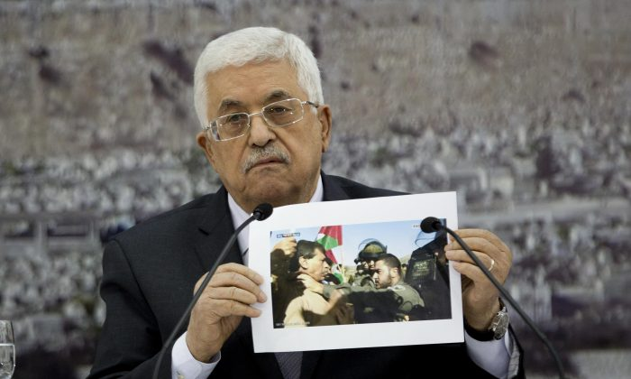 In this Dec. 10, 2014 file photo, Palestinian President Mahmoud Abbas holds a picture of an Israeli soldier pushing Palestinian Cabinet minister Ziad Abu Ain during a meeting of the Palestinian leadership at his compound in the West Bank city of Ramallah, Wednesday, Dec. 10, 2014.  (AP Photo/Majdi Mohammed, File)