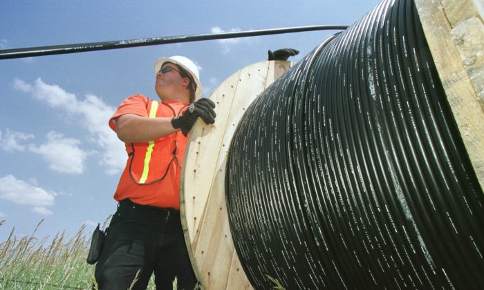 Reeltender Mo Laussie watches fiber-optic cable as he helps install the cable unto telephone poles June 21, 2001 in Louisville, CO. (Photo by Michael Smith/Getty Images)