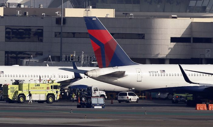 A Delta Air Lines jet, right, sits parked after making an emergency landing at Los Angeles International Airport, Tuesday, Jan. 13, 2015. The Boeing 757 experienced a mechanical problem soon after takeoff on a flight from Los Angeles to Minneapolis and had to circle off the Southern California coast for about an hour to burn fuel before landing safely back at the airport. (AP Photo/Nick Ut)