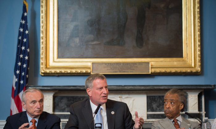 New York Mayor Bill de Blasio (C) is seated between New York City Police Commissioner William Bratton (L) and the Rev. Al Sharpton during a round table discussion convened to ease tensions over the death of Eric Garner, a black man who died from a police choke hold while being arrested. De Blasio has been unable to heal the deepening rift with the NYPD and erase the perception that he is not supporting the police. (AP Photo/New York City Mayoral Photography Office, Bob Bennett)