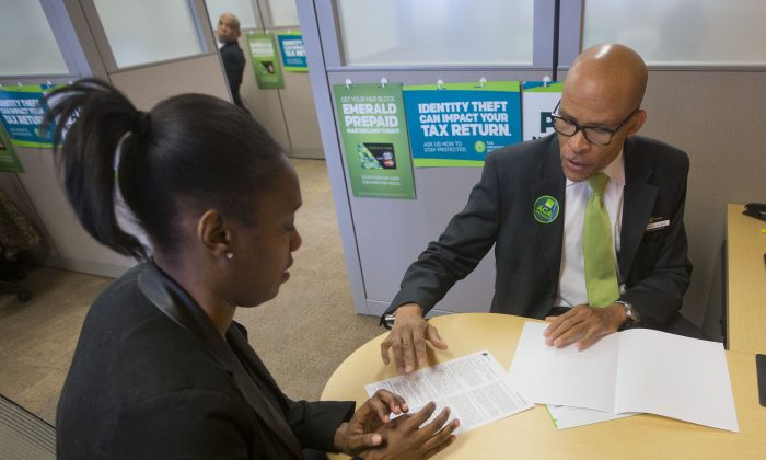 Tax preparer Richard Sowell, (R), works with Courtney Mayhew at H&R Block in Atlas District in Washington on Jan. 8, 2015.  Tax  preparers may get new clients this year, as people navigate Obamacare tax changes. (AP Photo/Pablo Martinez Monsivais)