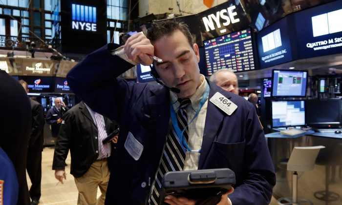 Trader Gregory Rowe wipes his forehead as he works on the floor of the New York Stock Exchange Wednesday, Jan. 14, 2015. (AP Photo/Richard Drew)