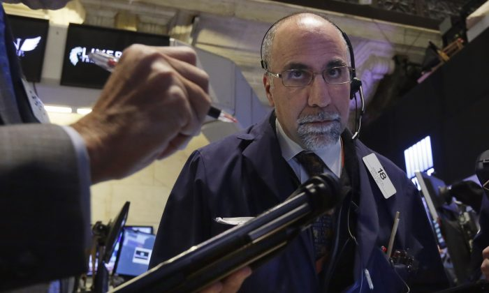 Trader John Liotti works on the floor of the New York Stock Exchange, Wednesday, Jan. 14, 2015. (AP Photo/Richard Drew)