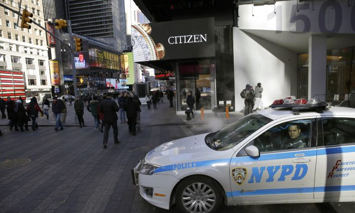 A policeman looks out the window of his patrol car in Times Square in New York. (AP Photo/Seth Wenig)