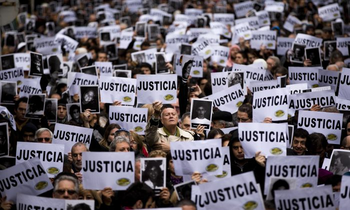 "People hold up signs that read in Spanish: ""Justice"" and pictures of the victims of the bombing of the Argentine-Israeli Mutual Association community center on the 19th anniversary of the terrorist attack, in Buenos Aires, Argentina, on July 18, 2013. In a statement released Wednesday, Jan. 14, 2015, Argentine Prosecutor Alberto Nisman, who is investigating the 1994 bombing of the Jewish community center, accused President Cristina Fernandez of reaching a deal with Iran to avoid punishing those responsible. (AP Photo/Victor R. Caivano)"