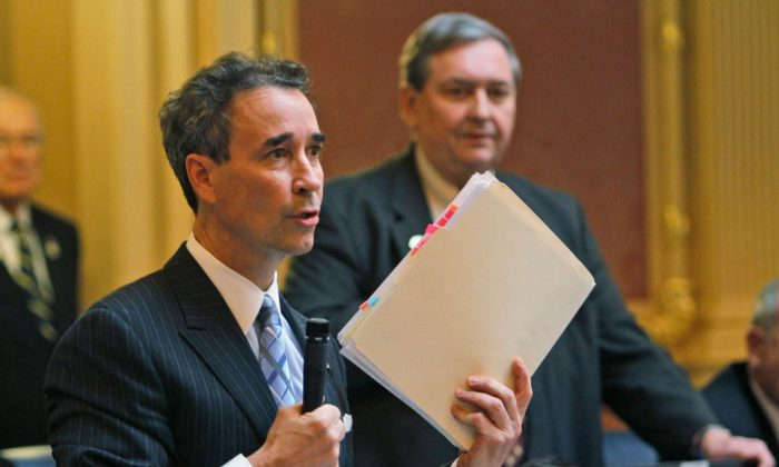 Del. Joe Morrissey (D-Henrico) holds papers during a debate on a bill that would end the state mandate for girls to receive the HPV vaccine during House session at the Capitol in Richmond, Va., on Jan. 26, 2012. Jailed Virginia lawmaker Morrissey was able to win a special election because enough voters apparently weren't bothered by his sex-scandal conviction. But whether he'll find enough support among his colleagues to remain in the House of Delegates is another matter. Morrissey, who defeated two opponents Tuesday night, Jan. 13, 2015, will return to a legislative body whose leaders have been researching the process for expelling him. (AP Photo/Steve Helber)