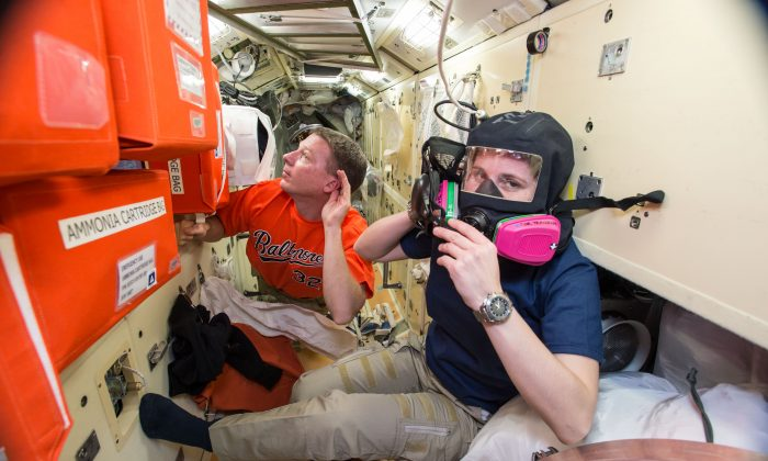 Image provided by NASA taken during a training exercise, US astronaut Terry Virts (L), assists European Space Agency astronaut Samantha Cristoforetti with emergency training aboard the International Space Station, on Dec. 1, 2014. Astronauts evacuated the US section of the International Space Station and moved to its Russian module after a problem emerged Wednesday, Jan. 14, 2015. (AP Photo/NASA)