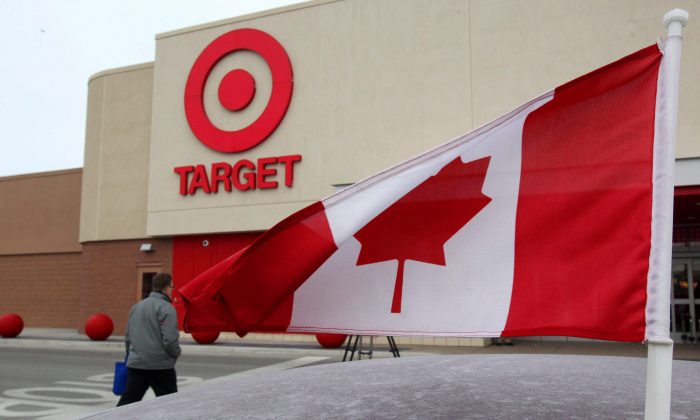In this March 5, 2013 photo, a Canadian flag flies on the car of a customer's car parked in front of a Target store in Guelph, Ontario. On Thursday, Jan. 15, 2015, Target said it plans to exit Canada, citing the company didn't foresee operations being profitable there until at least 2021. (AP Photo/The Canadian Press, Dave Chidley)