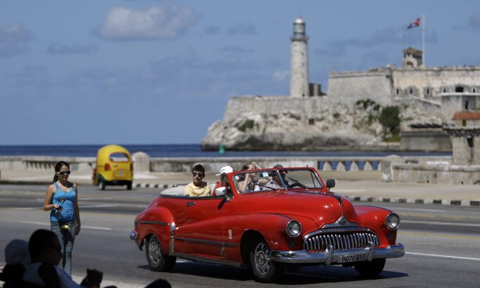 In this Oct 12, 2013 photo, tourists ride in a classic American car on the Malecon in Havana, Cuba. A new set of U.S. government regulations takes effect Friday, Jan. 16, 2015, severely loosening the 50-decade long travel and trade restrictions for Cuba. (AP Photo/Franklin Reyes)
