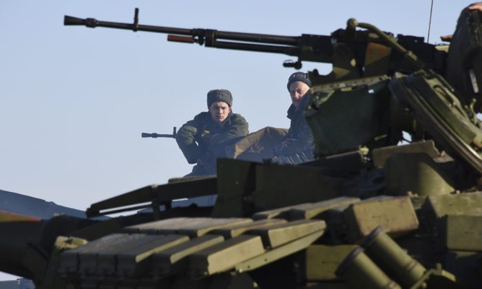 In this Wednesday, Jan. 14, 2015 photo Russian-backed separatist sit on top a tank at the check-point north of Luhansk, Eastern Ukraine.  An attack on a passenger bus in eastern Ukraine killed 12 people Tuesday, likely dealing the final blow to hopes that a short-lived and shaky cease-fire could take hold. (AP Photo/ Mstyslav Chernov)