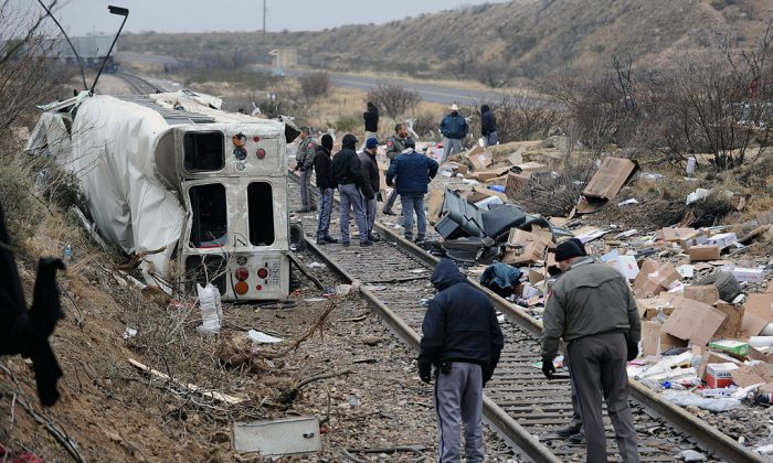 Authorities investigate the scene of a prison bus crash, Wednesday, Jan. 14, 2015, in Penwell, Texas. Law enforcement officials said the bus, carrying prisoners and corrections officers, fell from an overpass in West Texas and collided with a passing freight train, killing at least 10 people. (AP Photo/Odessa American, Mark Sterkel)