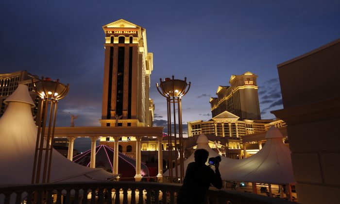 A man takes pictures of Caesars Palace hotel and casino, in Las Vegas, on Jan. 12, 2015. A cash-strapped division of casino giant Caesars Entertainment Corp. said early Thursday Jan. 15, 2015 that it filed for bankruptcy protection in Chicago, hoping the court agrees to its plan to get out from under $18.4 billion of debt. (AP Photo/John Locher)