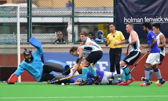 HKFC-A players scramble to get the ball away from their goal during an attack by Punjab-A in their HKHA Premier Division match at HKFC on Sunday Jan 11, 2015. (Bill Cox/Epoch Times)