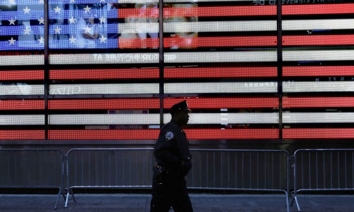 A police officer walks through Times Square in New York on Jan. 8, 2015. In bustling Times Square, where scores of tourists wander through streets clogged with traffic and hawkers selling trinkets, low-level enforcement activity had all but grinded to a halt. (AP Photo/Seth Wenig)