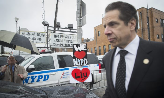 New York Gov. Andrew Cuomo (R) leaves the wake of New York Police Department officer Wenjian Liu at Aievoli Funeral Home in New York on Saturday, Jan. 3, 2015. Black law enforcement organizations in New York criticize Cuomo for not discussing legislative proposals with them. (AP Photo/John Minchillo)