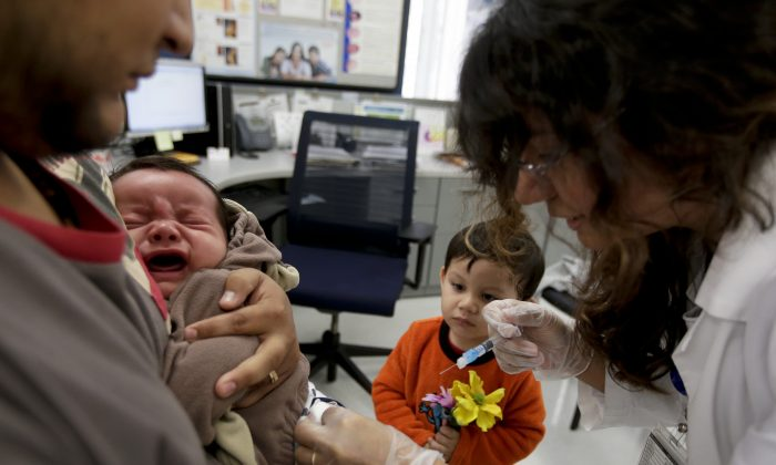 Julietta Losoyo (R), a registered nurse at the San Diego Public Health Center, gives Derek Lucero a whooping cough injection while in his father Leonel's arms as his brother Iker, 2, looks on, on Dec. 10, 2014. (AP Photo/Chris Carlson)