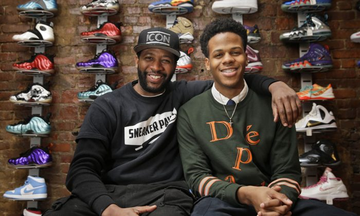 Entrepreneurs Chase Reed (R) and his father Troy Reed pose for a picture in their store in the Harlem section of New York on Jan. 12, 2015. The Reeds run Sneaker Pawn, a store that capitalizes on America's multi-billion dollar athletic footwear market and the high prices sneakers can get being re-sold. (AP Photo/Seth Wenig)