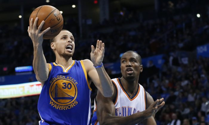 Golden State Warriors guard Stephen Curry (30) goes in for a shot in front of Oklahoma City Thunder forward Serge Ibaka (9) during the second quarter of an NBA basketball game in Oklahoma City, Friday, Jan. 16, 2015. (AP Photo/Sue Ogrocki)