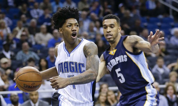 Orlando Magic's Elfrid Payton, left, looks to pass the ball as he drives around Memphis Grizzlies' Courtney Lee (5) during the first half of an NBA basketball game, Friday, Jan. 16, 2015, in Orlando, Fla. (AP Photo/John Raoux)