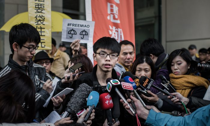 Student activist Joshua Wong (C) talks to the media outside the Wanchai police station in Hong Kong on Jan. 16, 2015. (Philippe Lopez/AFP/Getty Images)
