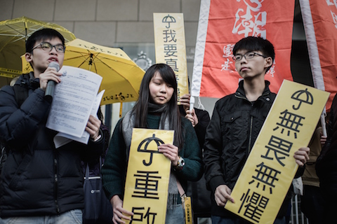 Student activist Joshua Wong (R) and other students display pro-democracy placards outside the Wanchai police station in Hong Kong on Jan. 16, 2015. (Philippe Lopez/AFP/Getty Images)